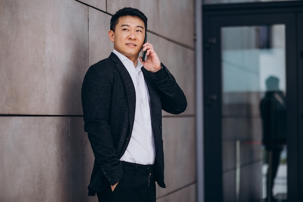 Junger hübscher asiatischer geschäftsmann im schwarzen anzug unter verwendung des telefons