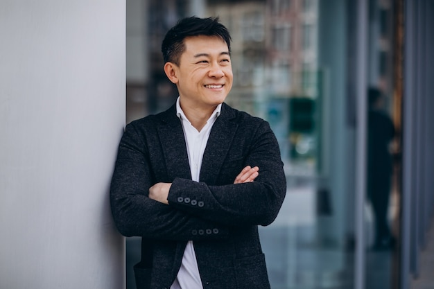 Junger hübscher asiatischer geschäftsmann im schwarzen anzug