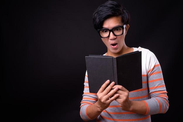 Junger hübscher asiatischer mann auf schwarz