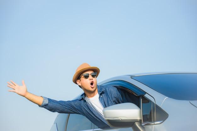 Junger hübscher asiatischer mann, der auto fährt, um an seiner feiertagsferienzeit mit schönem blauem himmel zu reisen.