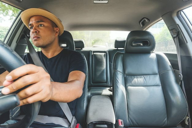 Junger hübscher asiatischer mann, der auto fährt