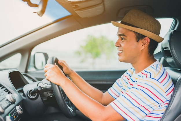 Junger hübscher asiatischer mann, der auto fährt.