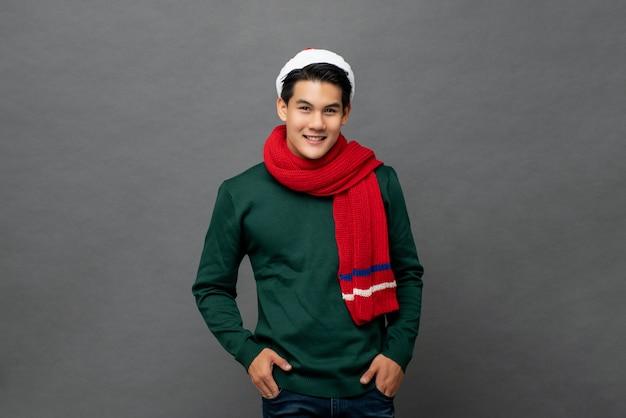 Junger hübscher asiatischer mann, der bunte rote und grüne weihnachtskleidung trägt