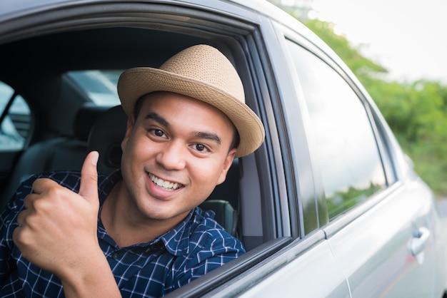 Junger hübscher asiatischer mann, der das auto sich zeigt daumen fährt.