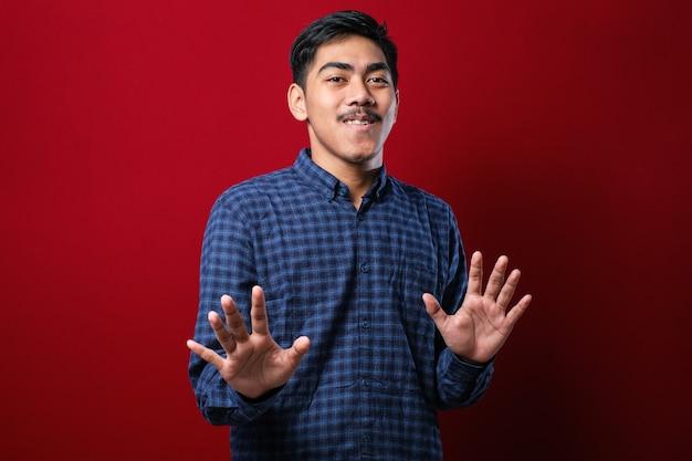 Junger hübscher asiatischer mann, der ein lässiges hemd trägt, das auf rotem hintergrund steht. handflächen wegziehen, die ablehnung und verleugnung mit ängstlichem und ekelhaftem ausdruck zeigen. stopp und verboten.