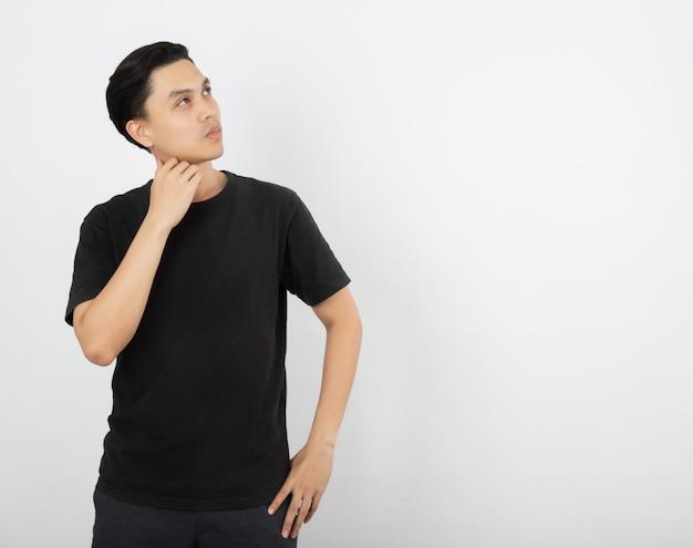 Junger hübscher asiatischer mann, der eine idee beim aufschauen denkt