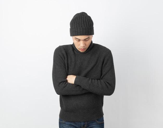 Junger hübscher asiatischer mann, der grauen pullover und mütze trägt, die sich umarmt und zittert, vor kaltem wind zittert und friert