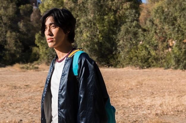 Junger hübscher asiatischer mann, der in natur geht
