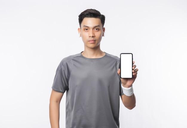 Junger hübscher asiatischer mann in sportausstattungen, die telefon mit leerem bildschirm zeigen