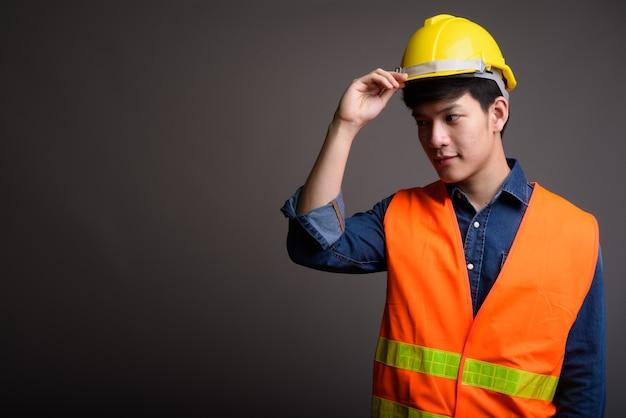 Junger hübscher asiatischer mannbauarbeiter auf grau