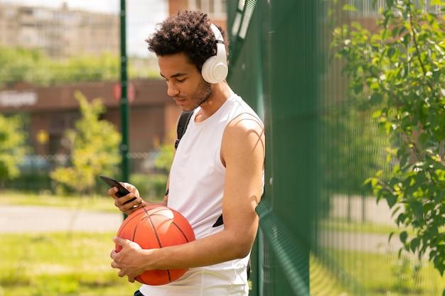 Junger hübscher athlet in der sportbekleidung, die musik in den kopfhörern hört und im smartphone nach dem spiel scroling