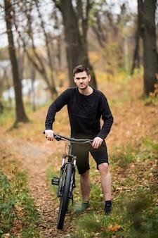 Junger hübscher athletischer mann, der mit fahrrad im bunten herbstpark steht. herbstsaison. männlicher radfahrer auf der straße mit gefallenen blättern