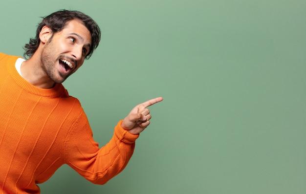 Junger hübscher ausdrucksstarker und überraschter indischer mann mit einem kopierraum