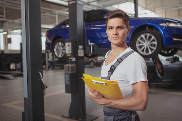 Junger hübscher automechaniker, der fahrzeug in seiner garage repariert