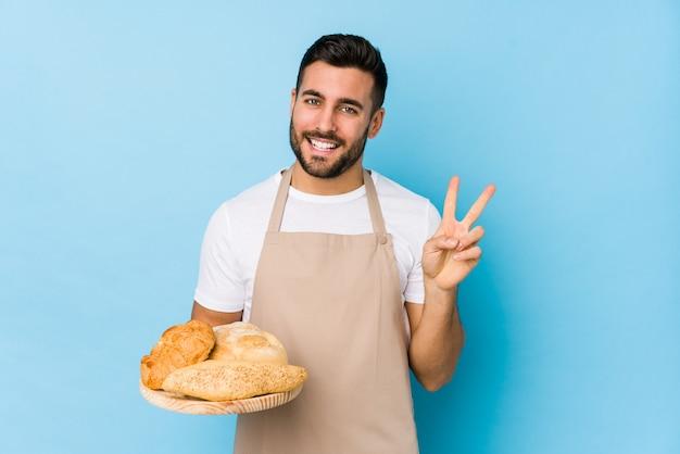 Junger hübscher bäckermann lokalisiert, nummer zwei mit den fingern zeigend.