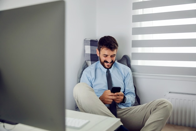 Junger hübscher bärtiger geschäftsmann, der in seinem büro sitzt und smartphone auf pause benutzt.