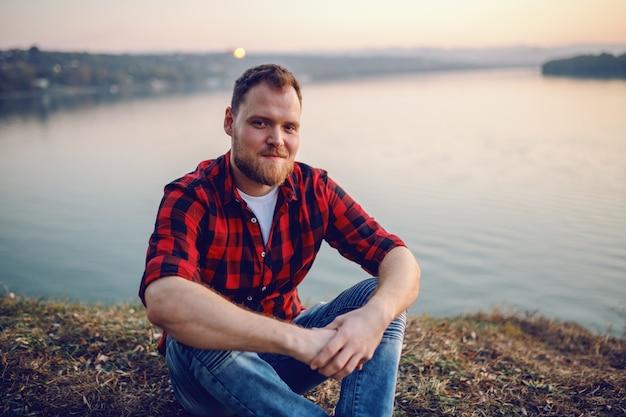 Junger hübscher bärtiger kaukasischer blonder mann im karierten hemd, der auf klippe am fluss sitzt.