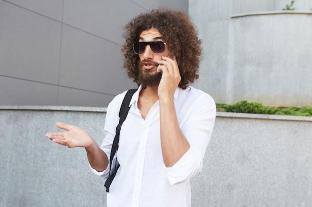 Junger hübscher bärtiger kerl mit dem gestikulierenden lockigen haar, während er etwas am telefon erklärt