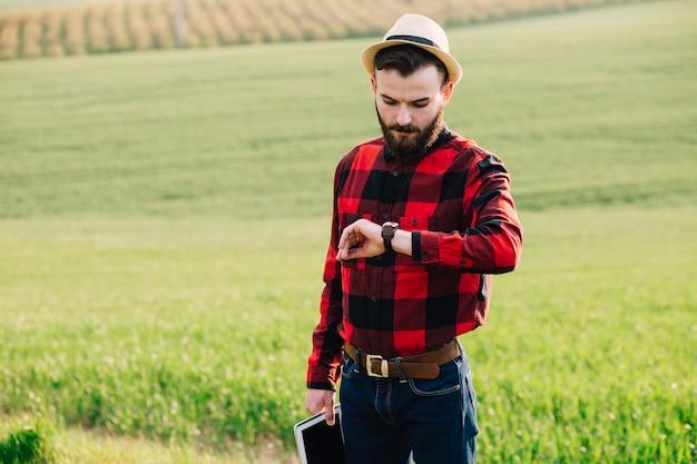 Junger hübscher bärtiger landwirt mit der tablette, die auf dem weizengebiet steht und auf der uhr schaut