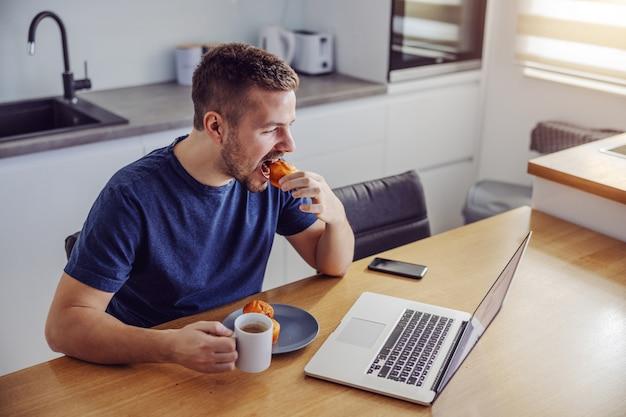 Junger hübscher bärtiger mann, der am esstisch sitzt, frühstückt und nachrichten auf laptop sieht.