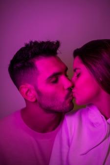 Junger hübscher bärtiger mann, der attraktive frau küsst
