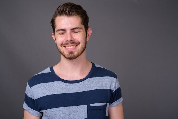 Junger hübscher bärtiger mann gegen graue wand