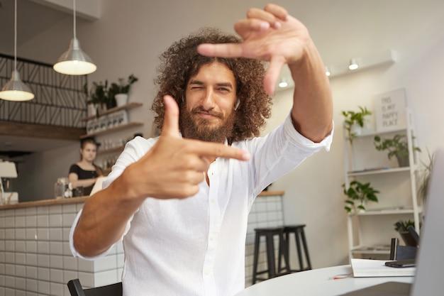 Junger hübscher bärtiger mann mit dem gelockten braunen haar, das schaut und lächelt, rahmengeste mit händen machend, unter verwendung der finger mit geschlossenem auge fokussierend
