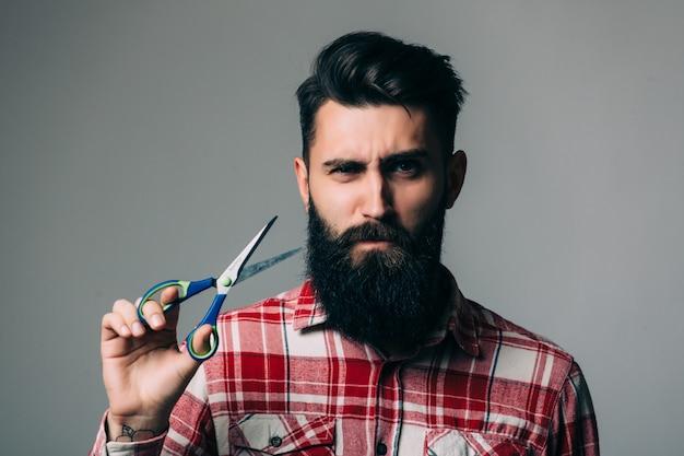 Junger hübscher bärtiger mann mit langem bartschnurrbart und brünettem haar, das friseur- oder friseurschere mit emotionalem gesicht auf grauer wand hält