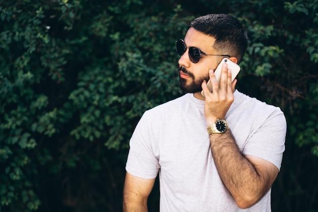 Junger hübscher bärtiger mann mit telefon