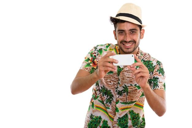Junger hübscher bärtiger persischer touristenmann, der telefon verwendet