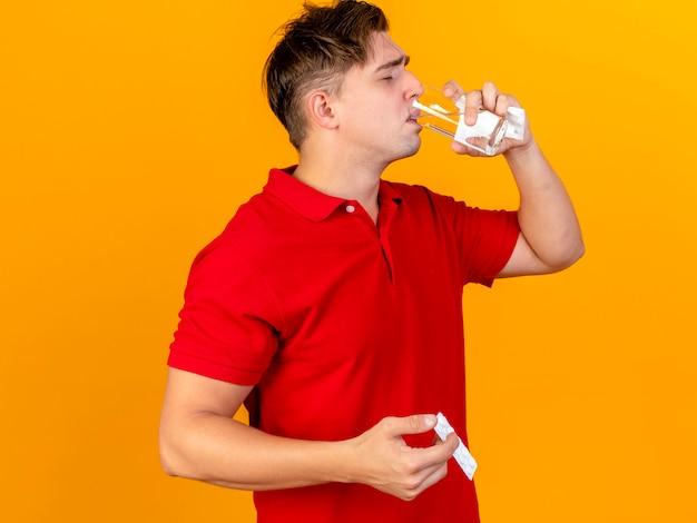 Junger hübscher blonder kranker mann, der serviette hält pille trinkwasser aus glas lokalisiert auf orange wand