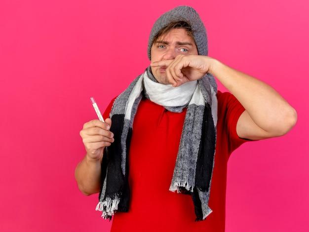 Junger hübscher blonder kranker mann, der wintermütze und schal hält, die thermometer halten, das kamera abwischt, die nase auf purpurrotem hintergrund mit kopienraum lokalisiert