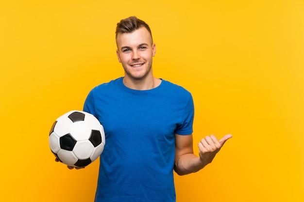 Junger hübscher blonder mann, der einen fußball über der lokalisierten gelben wand zeigt auf die seite hält, um ein produkt darzustellen