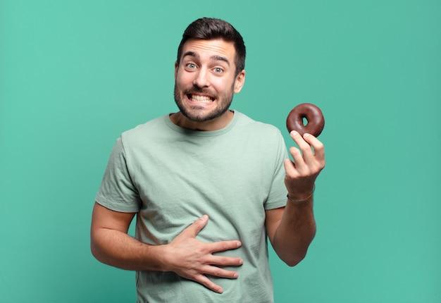 Junger hübscher blonder mann mit einem schokoladendonut. frühstückskonzept