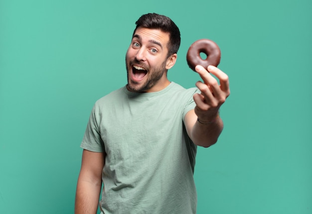 Junger hübscher blonder mann mit einem schokoladenkrapfen. frühstückskonzept