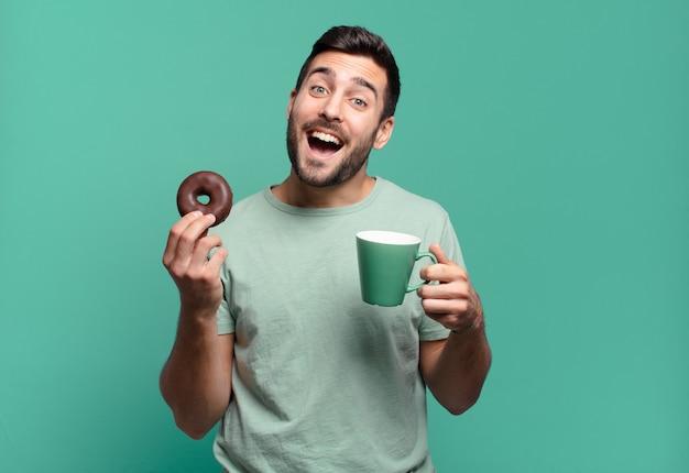 Junger hübscher blonder mann mit einem schokoladenkrapfen und einer kaffeetasse. frühstückskonzept