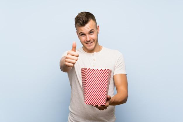 Junger hübscher blonder mann über der lokalisierten blauen wand, die eine schüssel popcorn hält