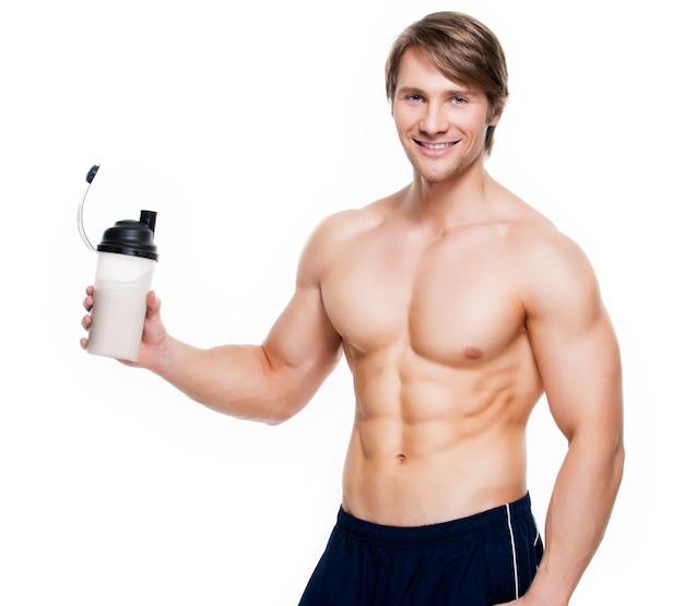 Junger hübscher bodybuilder mit einer flasche, die auf einer weißen wand aufwirft.