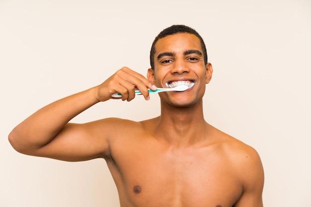 Junger hübscher brunettemann, der seine zähne putzt