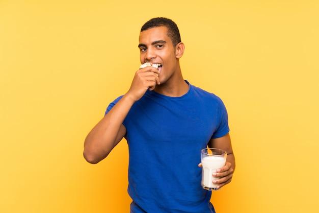 Junger hübscher brunettemann über der gelben wand, die frühstücksmilch isst und muffinkuchen hält