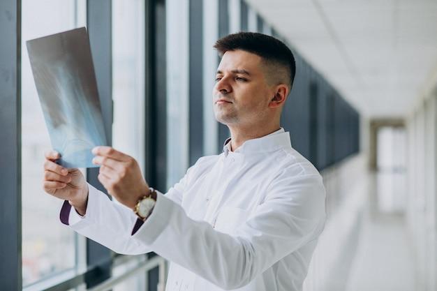 Junger hübscher chirurg, der den röntgenstrahl betrachtet
