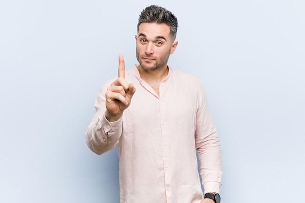 Junger hübscher cooler mann, der nummer eins mit finger zeigt