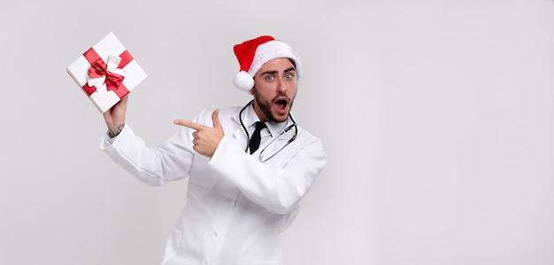 Junger hübscher doktor im weißen uniform- und santa claus-hut mit geschenk