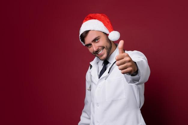 Junger hübscher doktor im weißen uniform- und santa claus-hut