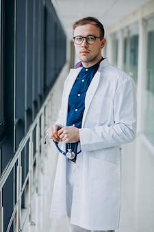 Junger hübscher doktor mit stethoskop an der klinik