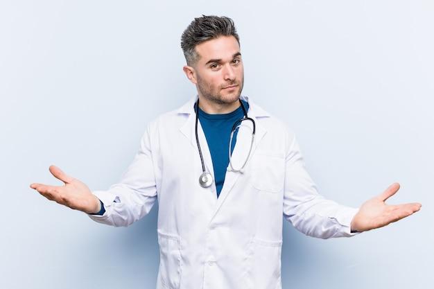 Junger hübscher doktormann, der einen willkommenen ausdruck zeigt.