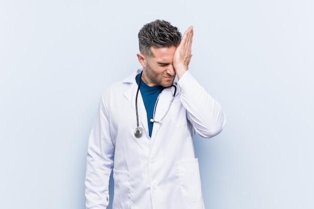 Junger hübscher doktormann, der etwas vergisst, stirn mit palme schlägt und augen schließt