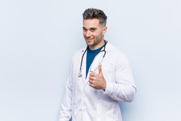 Junger hübscher doktormann, der oben daumen lächelt und anhebt