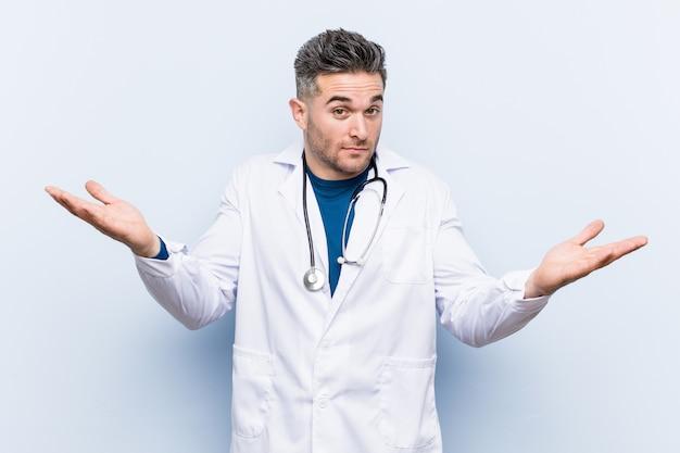 Junger hübscher doktormann, der schultern in fragender geste zweifelt und zuckt.