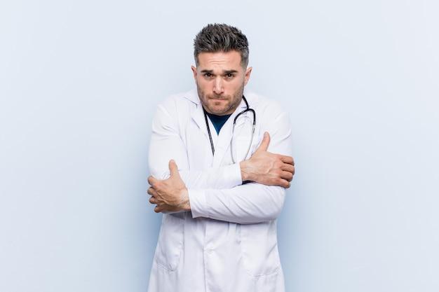 Junger hübscher doktormann, der wegen der niedrigen temperatur oder einer krankheit kalt geht